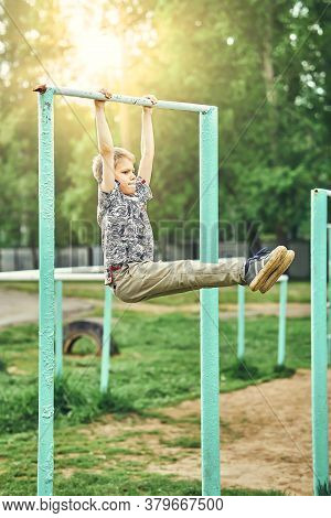 Full Body Side View Of Focused Preteen Boy In Casual Clothes Doing Exercises On Metal Bar While Spen