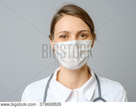 Happy Doctor Wearing Surgical Mask With Confidence In The Future To Solve The Crisis. Isolated On Gr