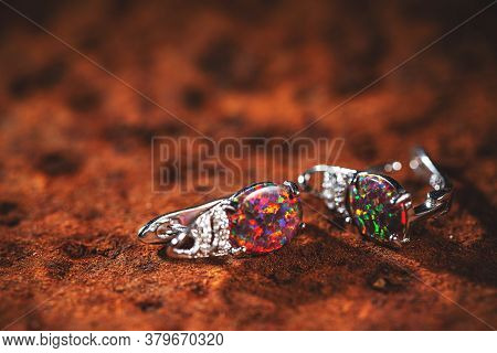 Woman Stylish Earrings In Colorful Colors On Brown Background