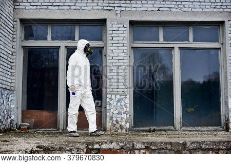 Full Length Of Male Environmentalist In Radiation Suit Holding Flask With Blue Liquid. Researcher We