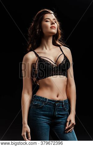 Young Woman In Lace Bra And Jeans With Closed Eyes Isolated On Black Background