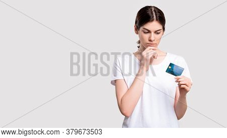 Bank Deposit. Financial Crisis. Doubtful Woman With Credit Card Concerned About Money Safety Isolate