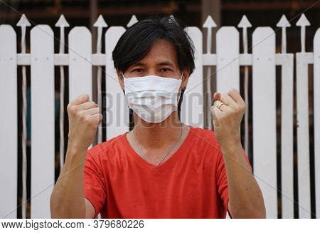 Masked Asian Man Prevent Germs. Tiny Particle Or Virus Corona Or Covid 19 Protection. Lift The Fist