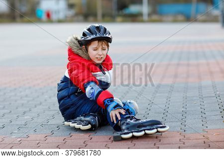Little School Kid Boy Skating With Rollers In The City. Child In Protection Safety Clothes. Active S