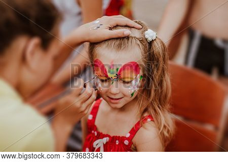Portrait Of Pretty Young Blond Girl In Red Summer Shirt At White Spots With Face-painting Like A Uni