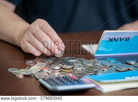 The Hands Of The Men Who Are Holding A Bank Passbook And Weaving A Budget.