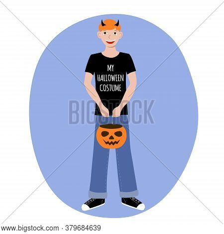 Red Haired Boy In A T Shirt With The Words My Halloween Costume And Horns On His Head. Pumpkin Candy