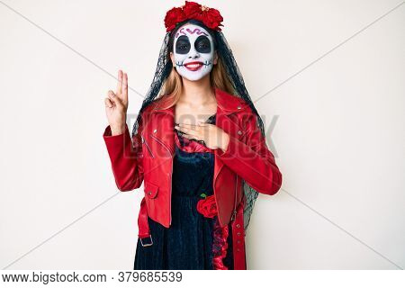 Woman wearing day of the dead costume over white smiling swearing with hand on chest and fingers up, making a loyalty promise oath