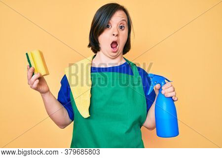 Brunette woman with down syndrome wearing apron holding scourer afraid and shocked with surprise and amazed expression, fear and excited face.