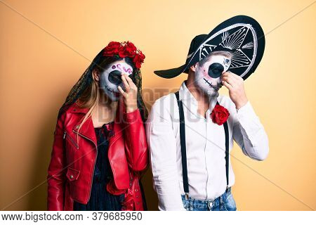 Couple wearing day of the dead costume over yellow tired rubbing nose and eyes feeling fatigue and headache. stress and frustration concept.