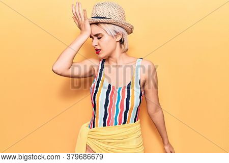 Young beautiful blonde woman wearing swimwear and summer hat surprised with hand on head for mistake, remember error. forgot, bad memory concept.