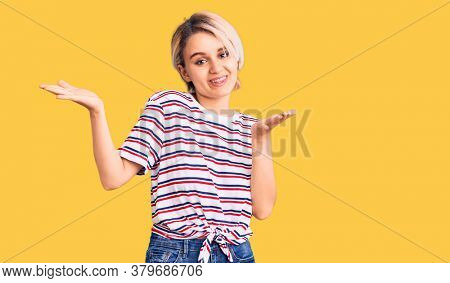 Young beautiful blonde woman wearing casual clothes clueless and confused expression with arms and hands raised. doubt concept.