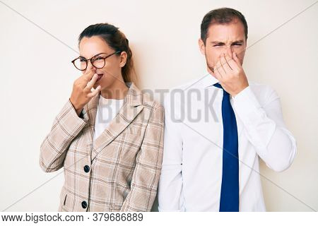 Beautiful couple wearing business clothes smelling something stinky and disgusting, intolerable smell, holding breath with fingers on nose. bad smell