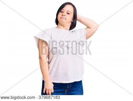 Brunette woman with down syndrome wearing casual white tshirt confuse and wondering about question. uncertain with doubt, thinking with hand on head. pensive concept.