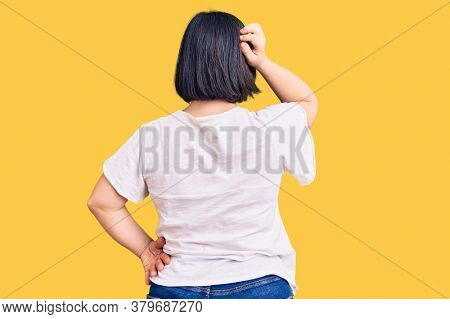 Brunette woman with down syndrome wearing casual white tshirt backwards thinking about doubt with hand on head