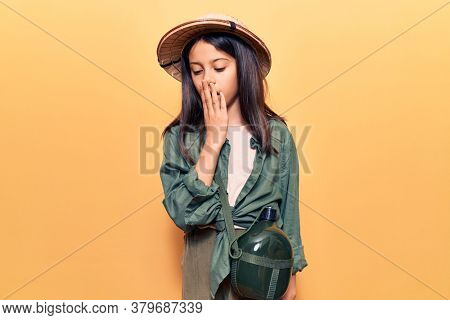 Beautiful child girl wearing explorer hat bored yawning tired covering mouth with hand. restless and sleepiness.
