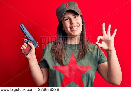 Young beautiful brunette woman wearing t-shirt with red star communist symbol holding gun doing ok sign with fingers, smiling friendly gesturing excellent symbol