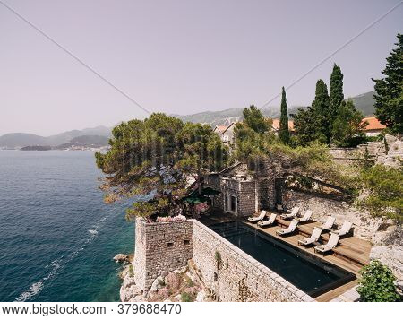 Sun Loungers For Sunbathing By The Pool, On The Island Of Sveti Stefan In Montenegro.