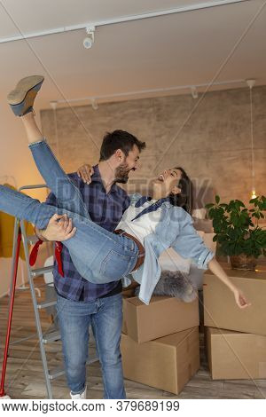 Beautiful Young Couple In Love Moving In Together, Having Fun While Unpacking Cardboard Boxes With T