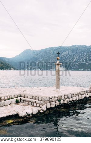 A Stone Pillar Beacon On The Island Against The Backdrop Of Mountains And Cloudy Sky. A Stone Column