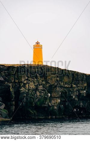 A Huge Orange Lighthouse On A Cliff In Iceland.