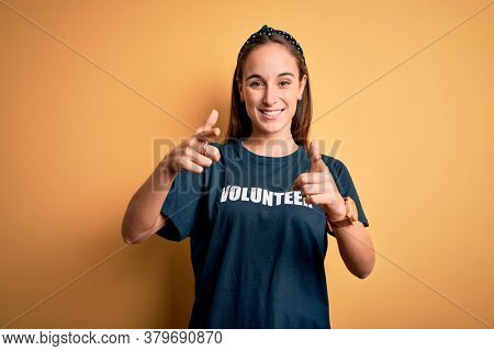 Young beautiful woman wearing volunteer t-shirt doing volunteering over yellow background pointing fingers to camera with happy and funny face. Good energy and vibes.