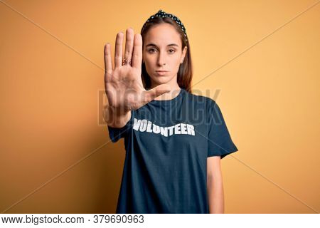 Young beautiful woman wearing volunteer t-shirt doing volunteering over yellow background doing stop sing with palm of the hand. Warning expression with negative and serious gesture on the face.
