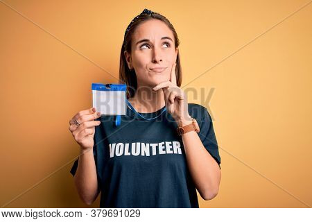 Young beautiful woman wearing volunteer t-shirt doing volunteering holding id pass card serious face thinking about question, very confused idea