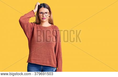 Beautiful young woman wearing casual clothes and glasses confuse and wonder about question. uncertain with doubt, thinking with hand on head. pensive concept.