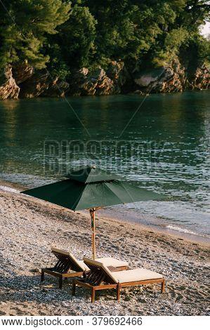 Luxurious Wooden Sun Loungers And Green Beach Umbrellas, On A Sandy Beach In Milocer Park, Near Svet