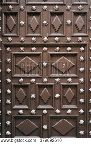 Brown Wood Door Texture With Many Metal Rivets And Diamond And Square Carvings.