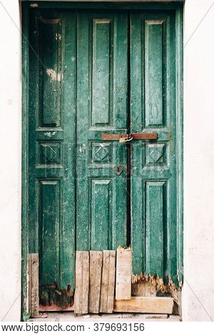 Close-up Of Shabby Green Wooden Doors Locked With A Broken Bottom And Planks At The Entrance.