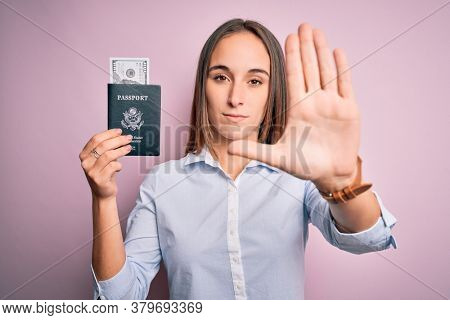 Tourist woman on vacation holding usa passport with dollars banknotes as a travel money with open hand doing stop sign with serious and confident expression, defense gesture