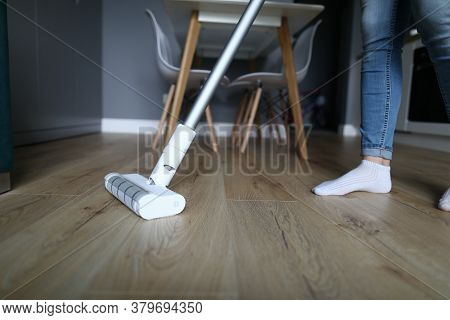 A Woman In Jeans And Socks Stands On A Laminate In An Apartment And Washes The Floor. Housewife Wipe