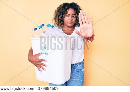 Young african american plus size woman holding recycling wastebasket with plastic bottles with open hand doing stop sign with serious and confident expression, defense gesture