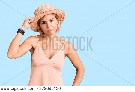 Young blonde woman wearing summer hat worried and stressed about a problem with hand on forehead, nervous and anxious for crisis