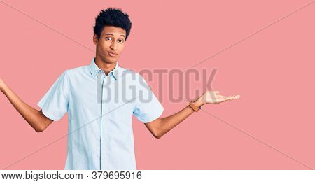 Young african american man wearing casual clothes clueless and confused expression with arms and hands raised. doubt concept.