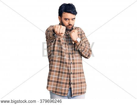 Young hispanic man wearing casual clothes punching fist to fight, aggressive and angry attack, threat and violence