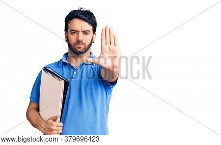 Young hispanic man holding notebook with open hand doing stop sign with serious and confident expression, defense gesture