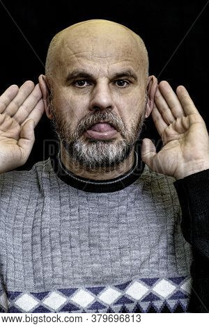 Bald Bearded Middle-aged Man Makes A Grimace With His Ears Sticking Out With His Hands And Sticking