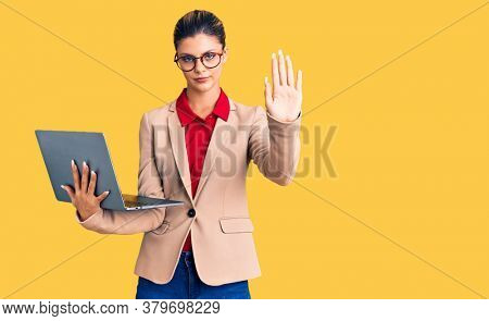 Young beautiful woman holding laptop with open hand doing stop sign with serious and confident expression, defense gesture
