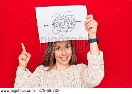 Young beautiful blonde woman holding a picture of chaos and stress smiling happy pointing with hand and finger to the side
