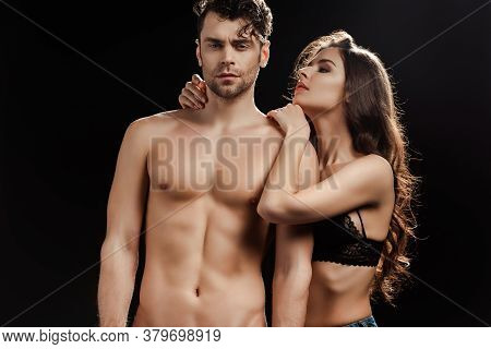 Attractive Woman In Bra Hugging Handsome Muscular Man Isolated On Black Background