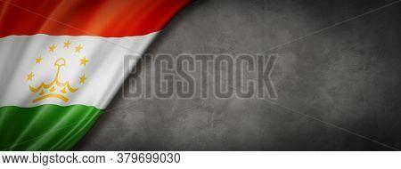 Tajikistan Flag On Concrete Wall. Horizontal Panoramic Banner. 3d Illustration