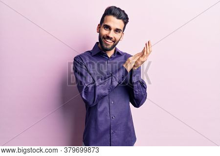 Young handsome man with beard wearing casual shirt clapping and applauding happy and joyful, smiling proud hands together