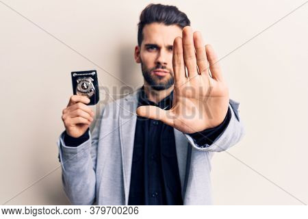 Young handsome man with beard holding police badge with open hand doing stop sign with serious and confident expression, defense gesture