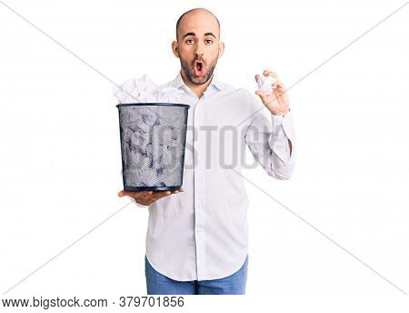 Young handsome man holding paper bin full of crumpled papers scared and amazed with open mouth for surprise, disbelief face