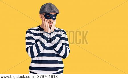 Young handsome man wearing burglar mask tired hands covering face, depression and sadness, upset and irritated for problem