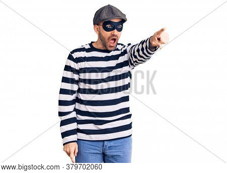 Young handsome man wearing burglar mask pointing with finger surprised ahead, open mouth amazed expression, something on the front