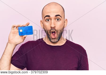 Young handsome bald man holding credit card scared and amazed with open mouth for surprise, disbelief face